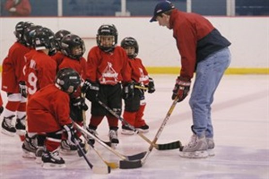 Children learning hockey from coach